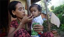A mother in Nepal feeds her child with peanut paste. She has two children 4ce9e7c37